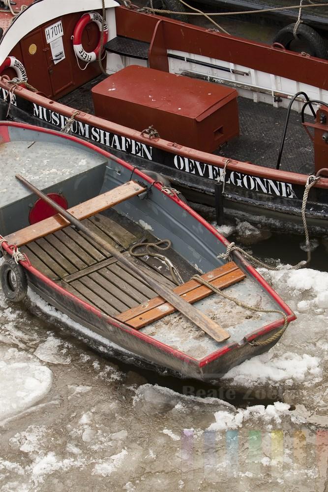 kleine, historische Barkasse und ein Ruderboot liegen im Hamburger Museumshafen Oevelgönne im Eis der Elbe fest