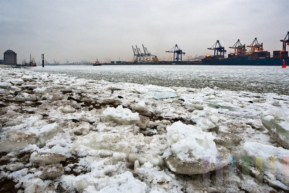 Blick über dicke Eisschollen am Strand von Hamburg-Oevelgönne zum Museumshafen und den Burchardkai