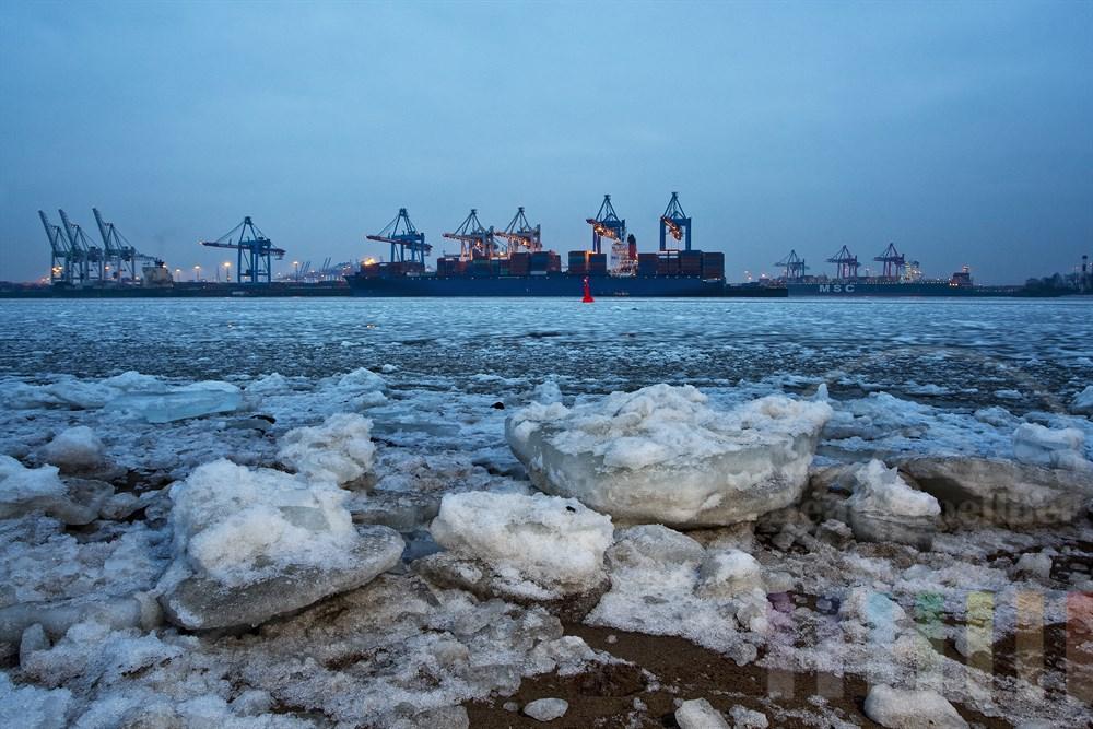 Frostiger Winternachmittag an der Elbe in Hamburg Övelgönne. Dicke Eisschollen liegen am Strand während der Betrieb an den Containerterminals ungehindert seinen Gang nimmt