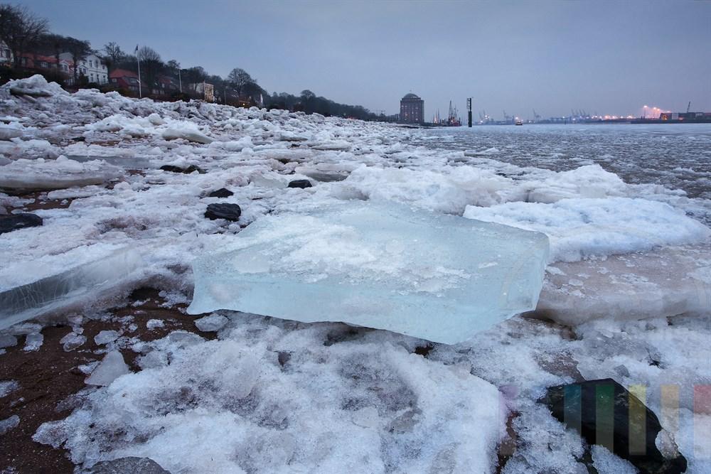 Blick über dicke Eisschollen am Strand von Hamburg-Oevelgönne zum Museumshafen