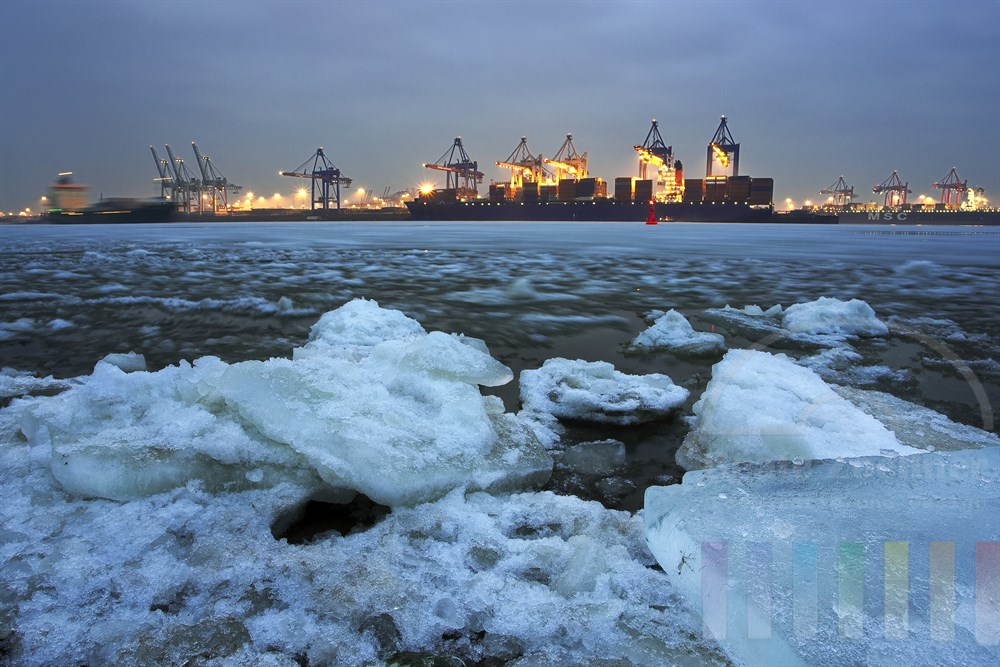 Blick über dicke Eisschollen am Strand von Hamburg-Oevelgönne auf einen Container-Terminal. Dort wird gerade ein Container-Schiff entladen