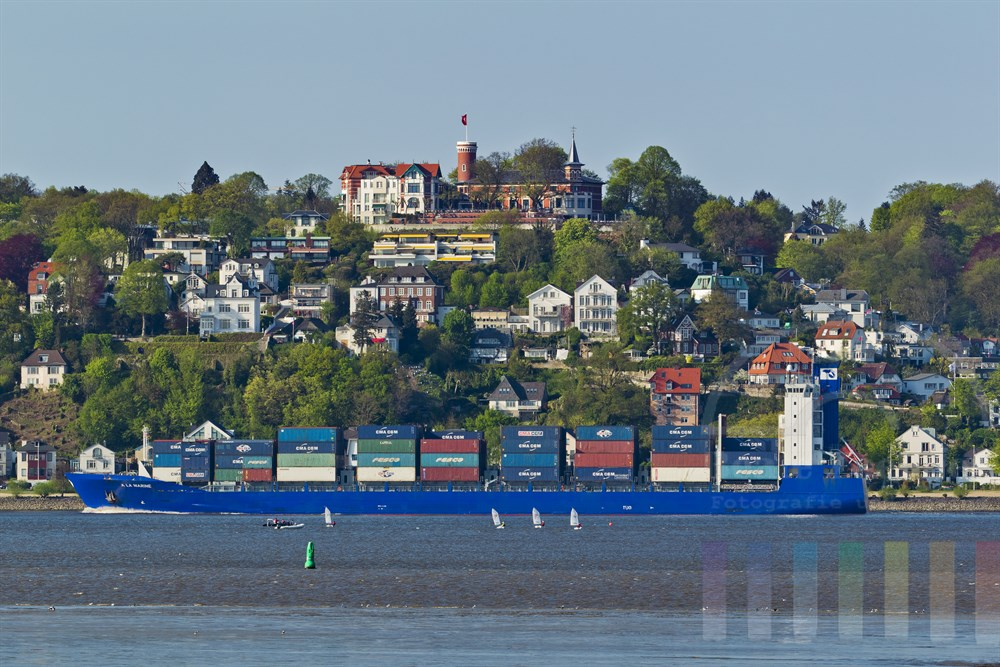 Blick vom suedlichen Elbufer bei Cranz auf den Suellberg und Hamburg-Blankenese - ein Containerschiff faehrt Richtung Elbmuendung, sonnig