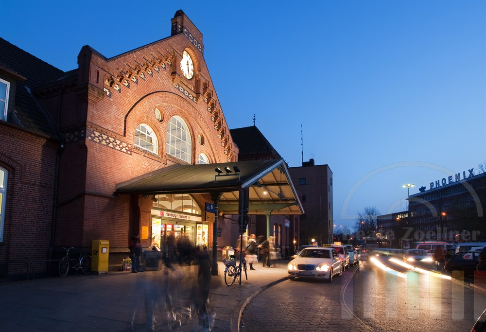 Blaue Stunde und Feierabendverkehr vor dem Bahnhof Hamburg-Harburg. Im Hintergrund der Firmensitz der Phoenix-Werke