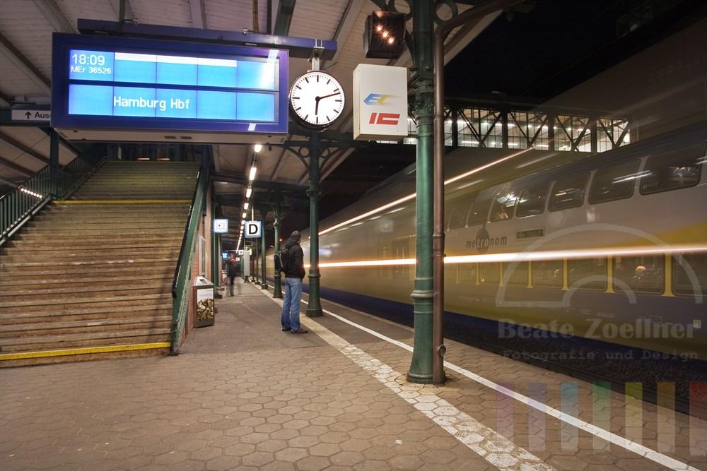 Abends: Auf dem Bahnsteig im Bahnhof Harburg - ein Metronom-Zug fährt ein