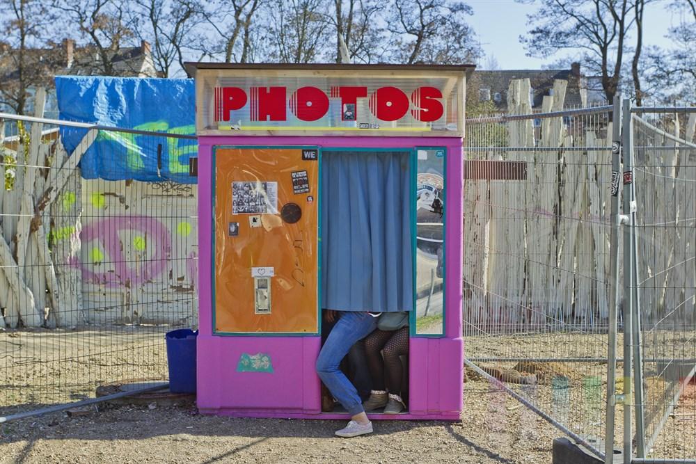 """Drei junge Maedchen sitzen hinter einem Vorhan in einen Passfotoautomaten an der Hamburger Max-Brauer-Allee (Hoehe Beach Club """"Central Park"""") und lassen sich fotografieren"""