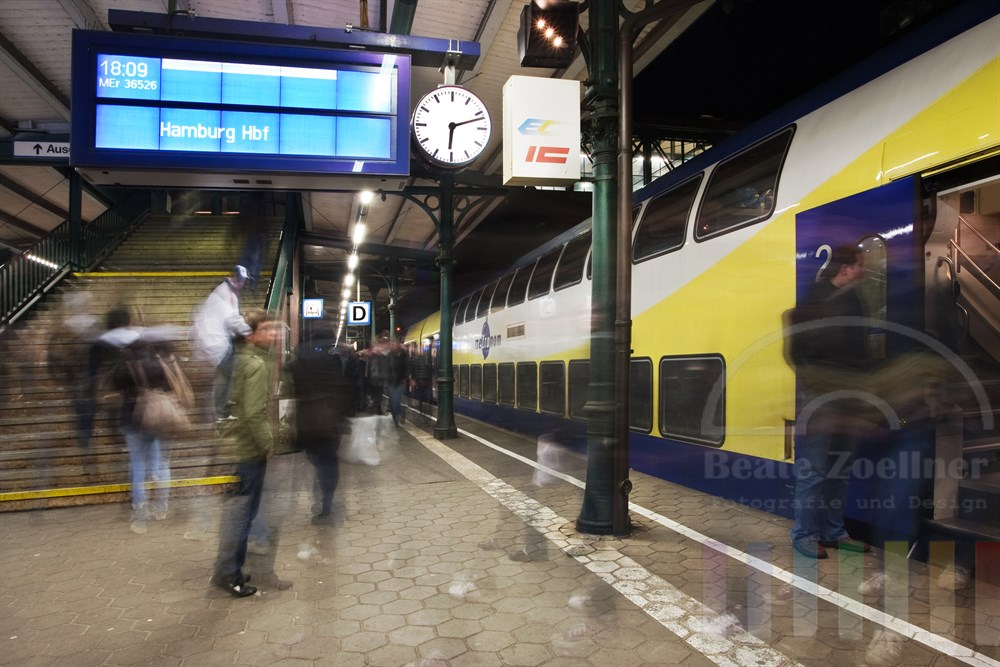 Ein- und Aussteigen der Fahrgaeste auf dem Bahnsteig - der Zug (ein Metronom) wartet