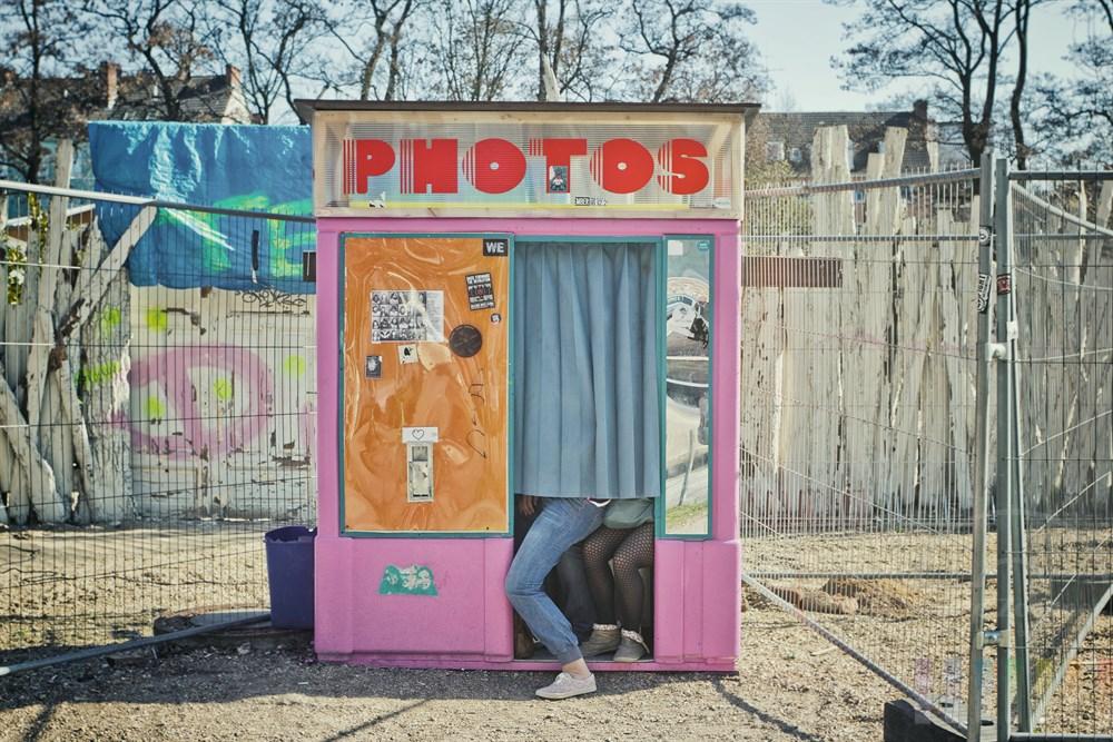 """Drei junge Maedchen sitzen hinter einem Vorhang in einen Passfotoautomaten an der Hamburger Max-Brauer-Allee (Hoehe Beach Club """"Central Park"""") und lassen sich fotografieren"""