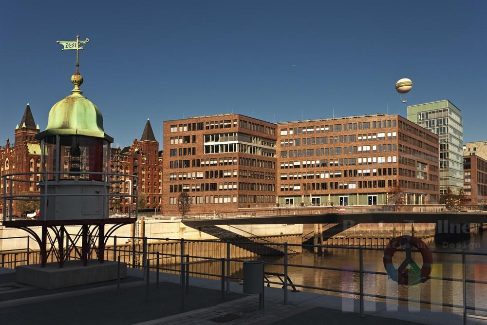 Blick von der Promenade unterhalb der Hamburger Osakaallee auf die Schnittstelle zwischen moderner Hafencity und historischer Speicherstadt, sonnig