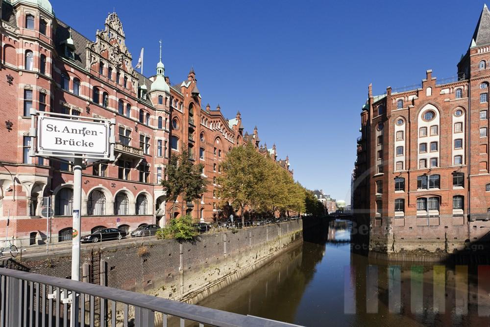 Blick von  der St. Annen-Bruecke in der Hamburger Speicherstadt auf die Strasse Hollaendischer Brook und die historischen Speicherfassaden am Fleet, sonnig