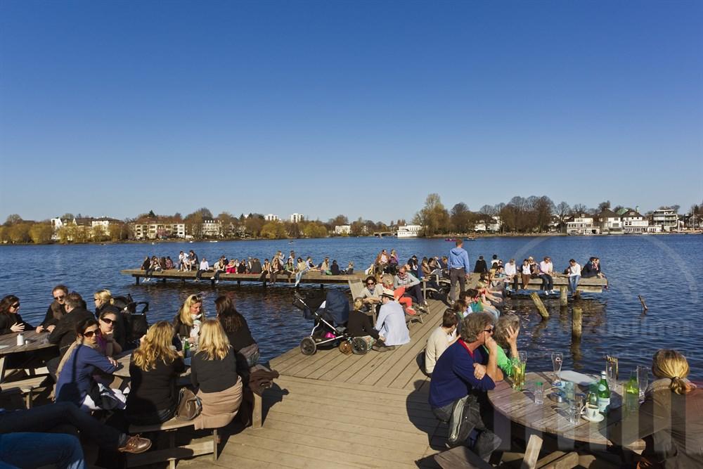 Blick ueber einen mit zahlreichen sonnenhungrigen Menschen besetzten Bootssteg auf das oestliche Ufer der Hamburger Aussenalster