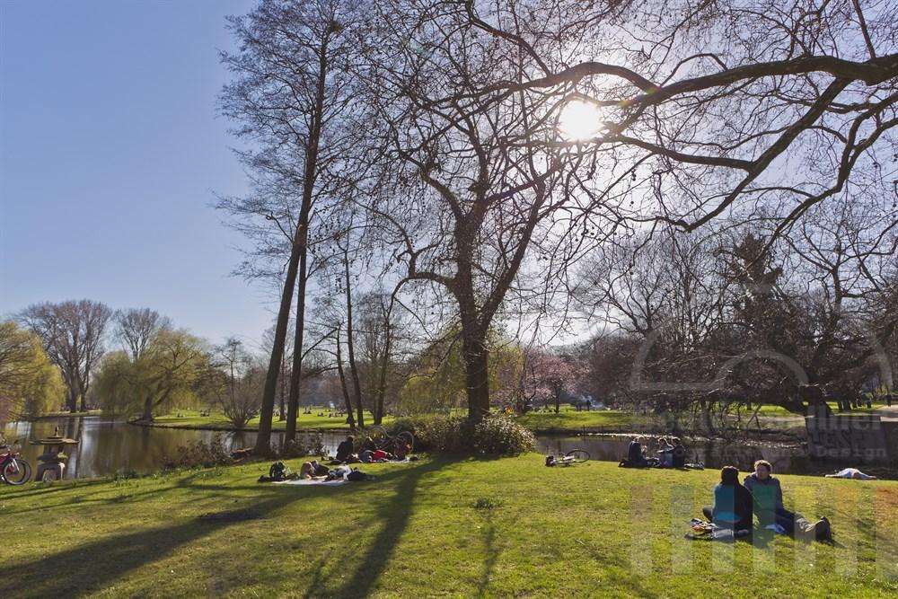 Menschen geniessen die Fruehlingssonne auf den Wiesen an der Hamburger Aussenalster