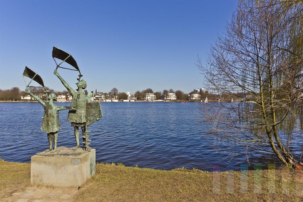 """Skulptur des Bildhauers Gerhard Brandes """"Drachensteigen lassende Kinder"""" von 1963 am westlichen Ufer der Hamburger Aussenalster, fruehlingshaft-sonnig"""