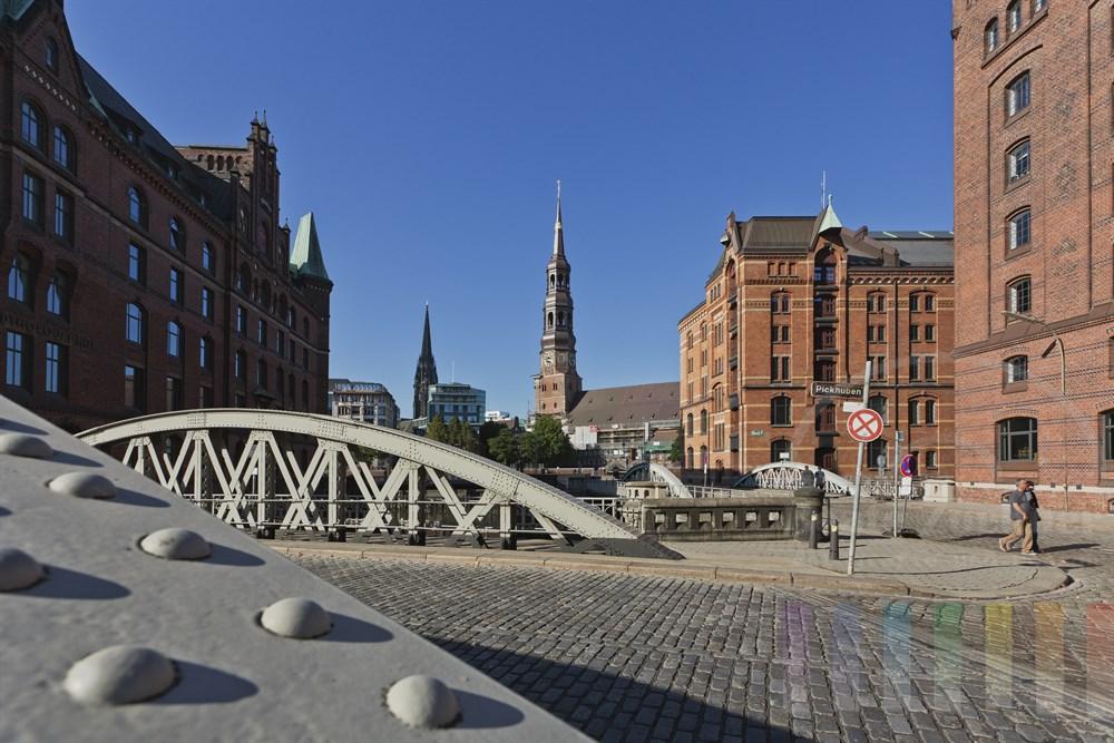 Blick von der Strasse Pickhuben in der historischen Hamburger Speicherstadt auf die Altstadt und die Kirche St. Katharinen und die Turm-Ruine der ehemaligen St. Nikolaikirche, sonnig