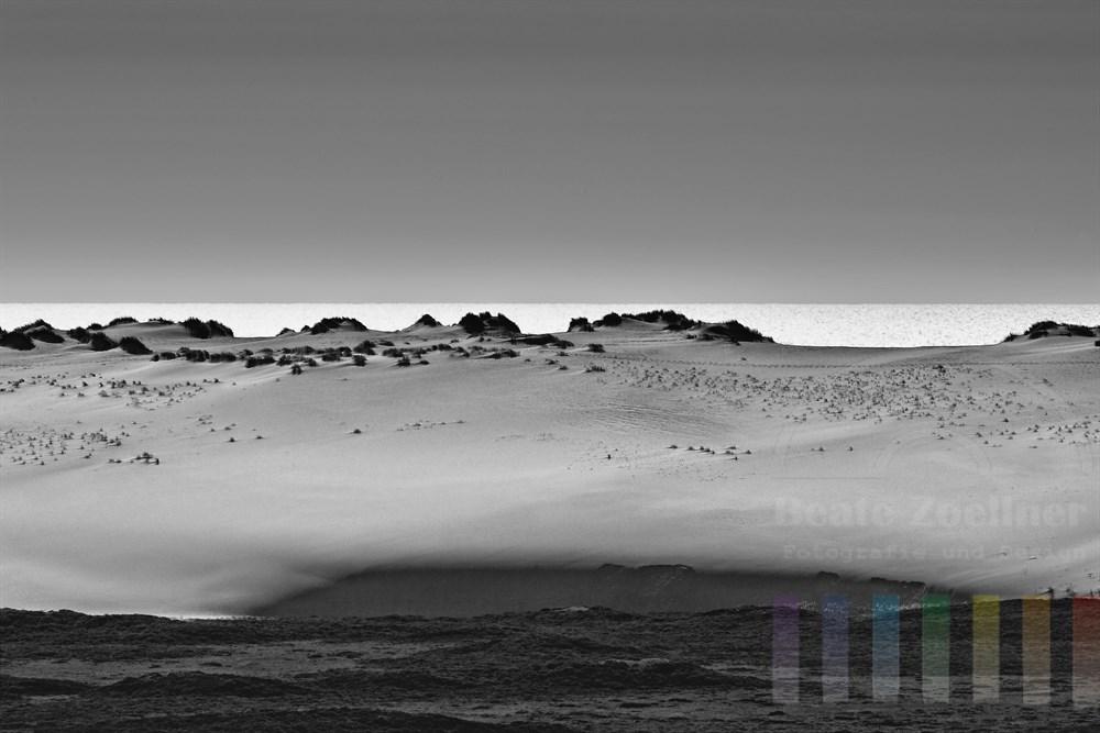 Blick auf eine der Wanderuenen in List auf Sylt und die im Sonnenlicht glitzernde Nordsee. Die Landschaft wirkt wie eine Wueste (schwarzweiss)