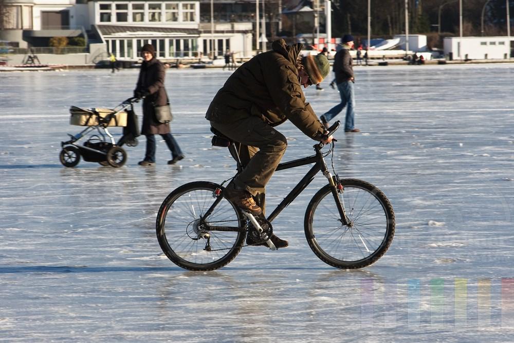 Radfahrer und Frau miot Kinderwagen auf der zugefrorenen Hamburger Aussenalster