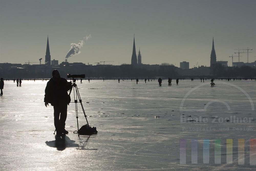 Fotograf im Gegenlicht auf der zugefrorenen Aussenalster in Hamburg nutzt den ungewohnten Blick auf die Stadt