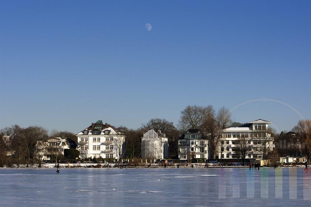 Mond steht am Nachmittag über der zugefrorenen Hamburger Aussenalster, auf der sich bereits einige Menschen tummel,
