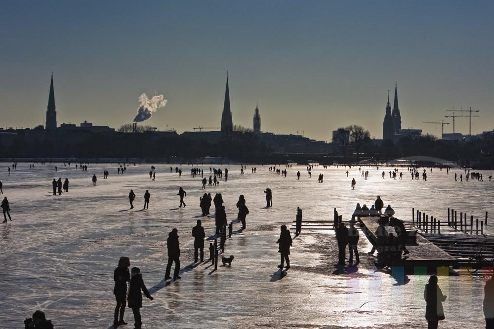 zahlreiche Menschen tummeln sich auf der zugefrorenen Aussenalster in Hamburg vor der Silhouette der Stadt