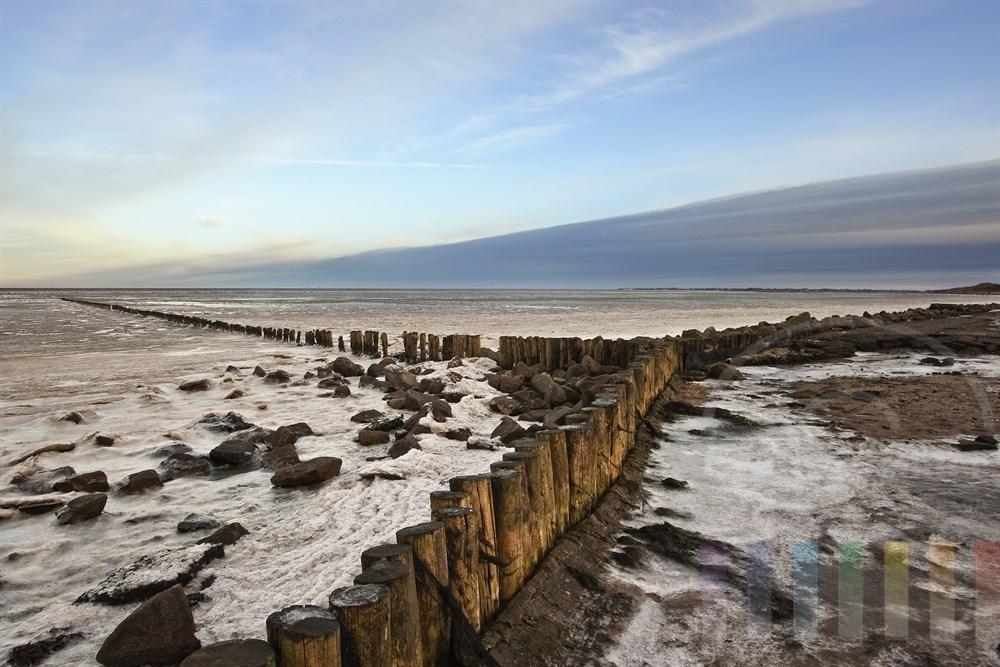 Schneewolkenfront steht über dem vereisten Wattenmeer der Insel Sylt, sonnig