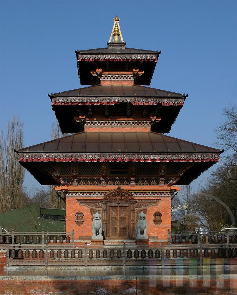 Hochformat: Nepaltempel am Eingang des Hamburger Tierparks Hagenbeck, Bäume noch unbelaubt, blauer Himmel, sonnig