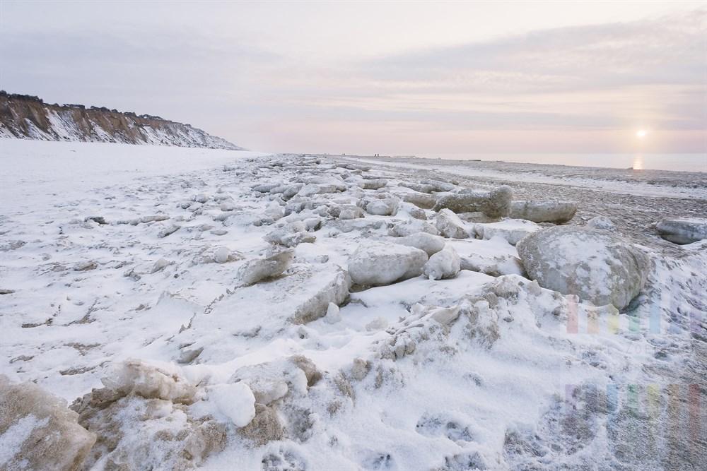 Mit Schnee und Eisschollen bedeckter Strand von Kampen/Sylt kurz vor Sonnenuntergang.