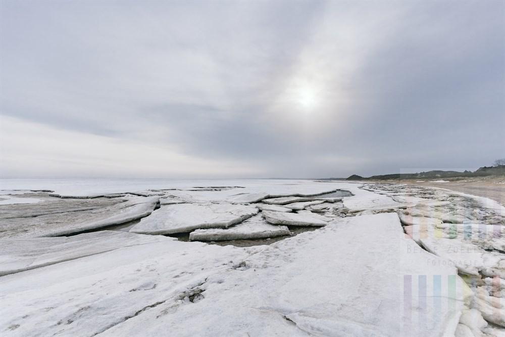 Langsam schmelzende und auseinander brechende Eisschollen liegen am Strand des Sylter Wattenmeeres