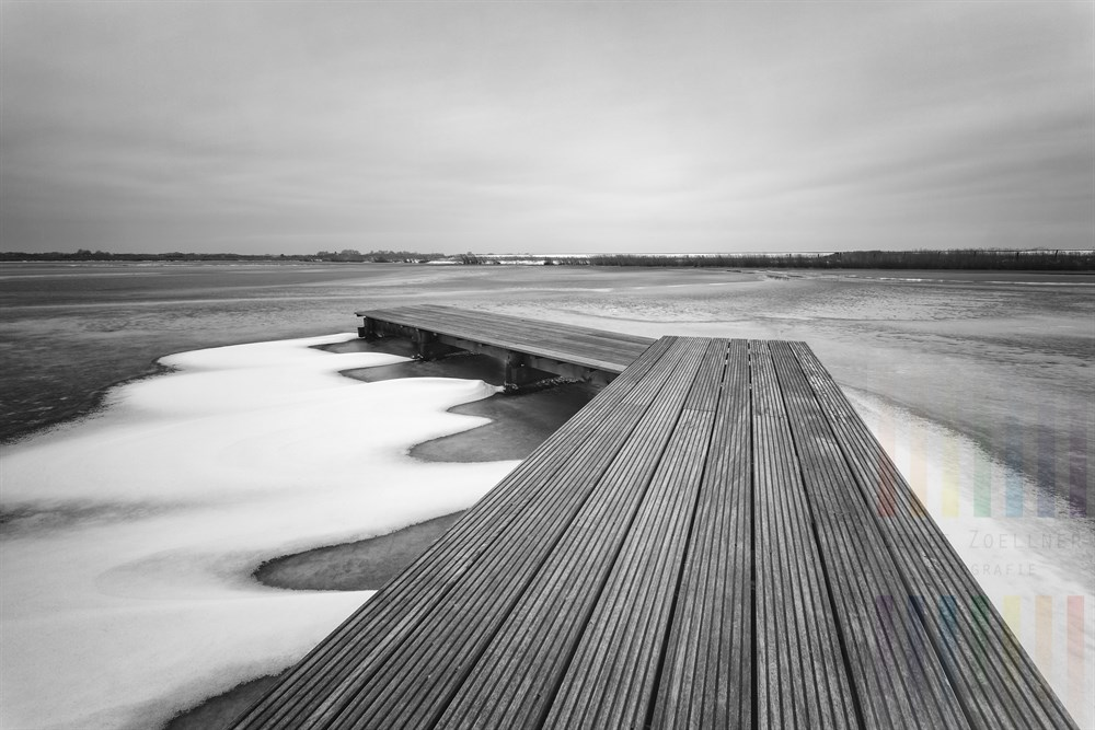 Hölzerner Angelsteg führt auf einen See hinaus, der mit noch mit einer dünnen, brüchigen Eisschicht bedeckt ist, grauer Himmel