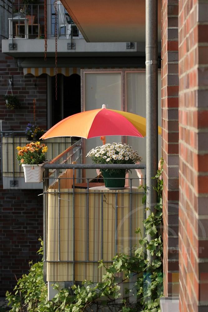 Hochformat: Balkon mit Margariten und buntem Sonnenschirm dekoriert