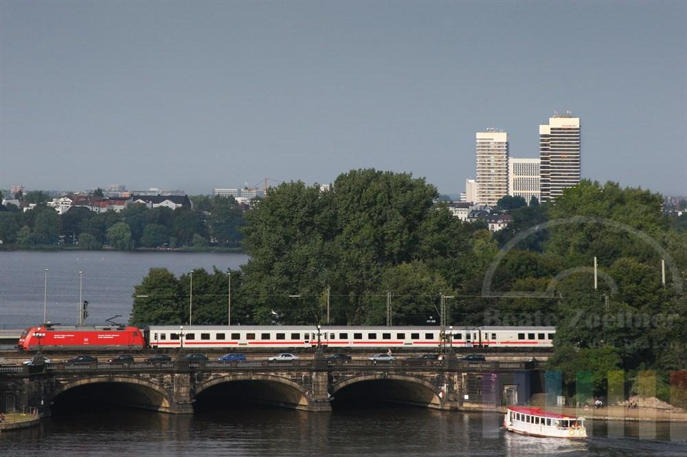 Blick aus der obersten Etage des Dresdner-Bank-Gebaeudes über die Binnenalster zur Lombardsbrücke, über die gerade ein Personen-Zug fährt, zur Außenalster. Am oberen rechten Bildrand sind die Mundsburg-Hochhaeuser zu erkennen