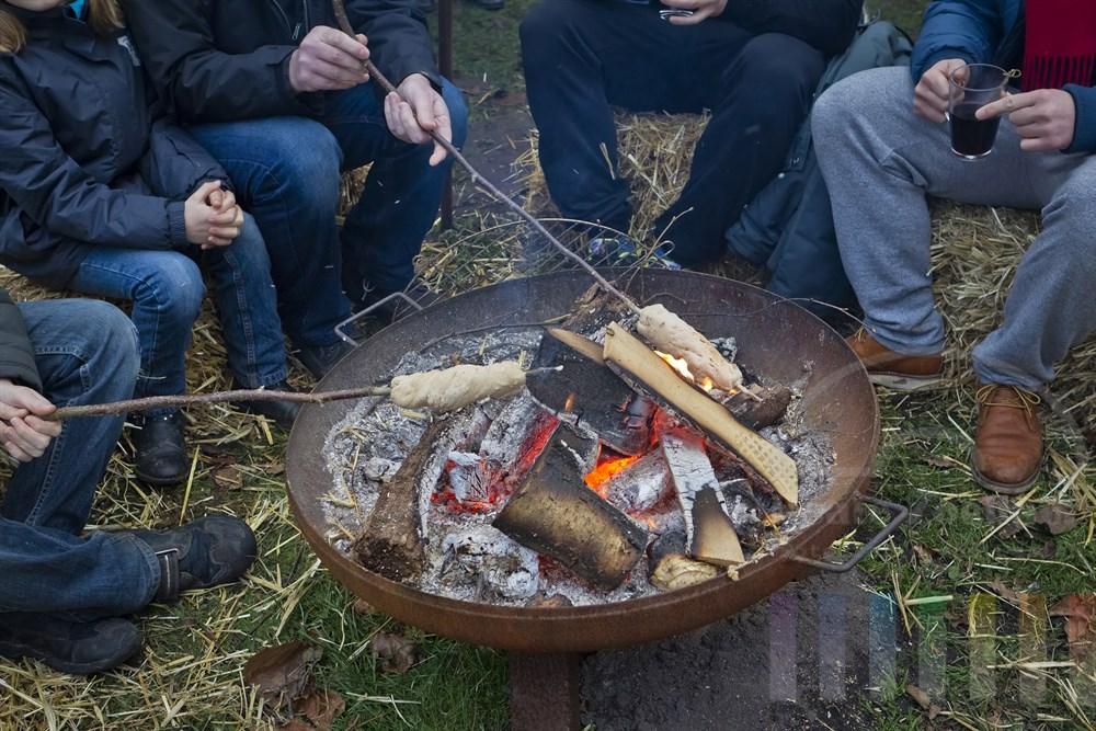 Erwachsene und Kinder sitzen auf dem Barmstedter Weihnachtsmarkt um eine offenen Feuerstelle und halten Äste mit Brotteig in die Glut - sie backen Stockbrot