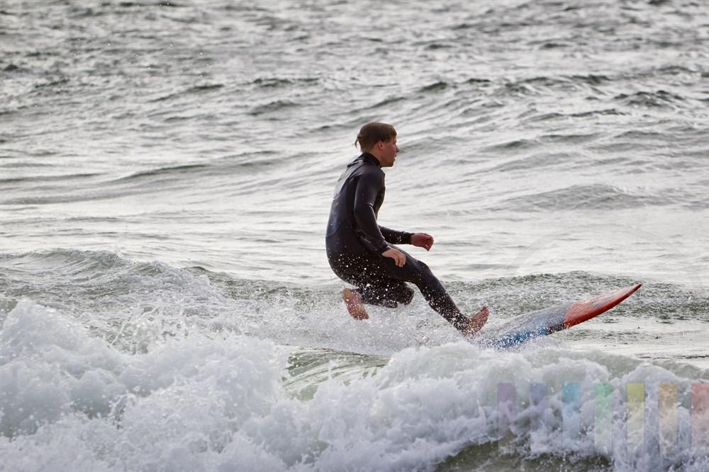 Junger Mann reitet auf seinem Surfbrett auf einer Nordseewelle vor der Küste Sylts
