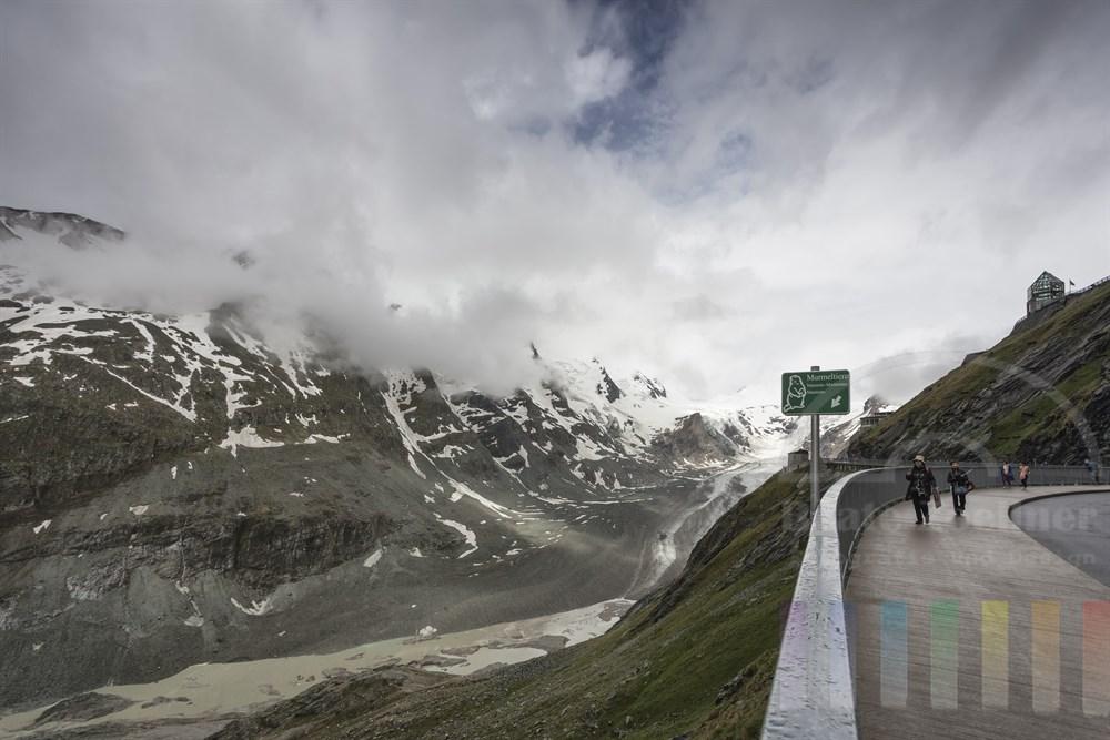 Regnerischer Tag an der Großglockner-Hochalpenstraße: Tief hängende Wolken verdecken den Blick zum Gipfel. Japanische Touristinnen spazieren an der Kaiser-Franz-Josefs-Höhe mit Blick auf die Reste des Pasterzen-Gletschers. Ein Schild am Geländer weist auf die am Hang lebenden Murmeltiere hin
