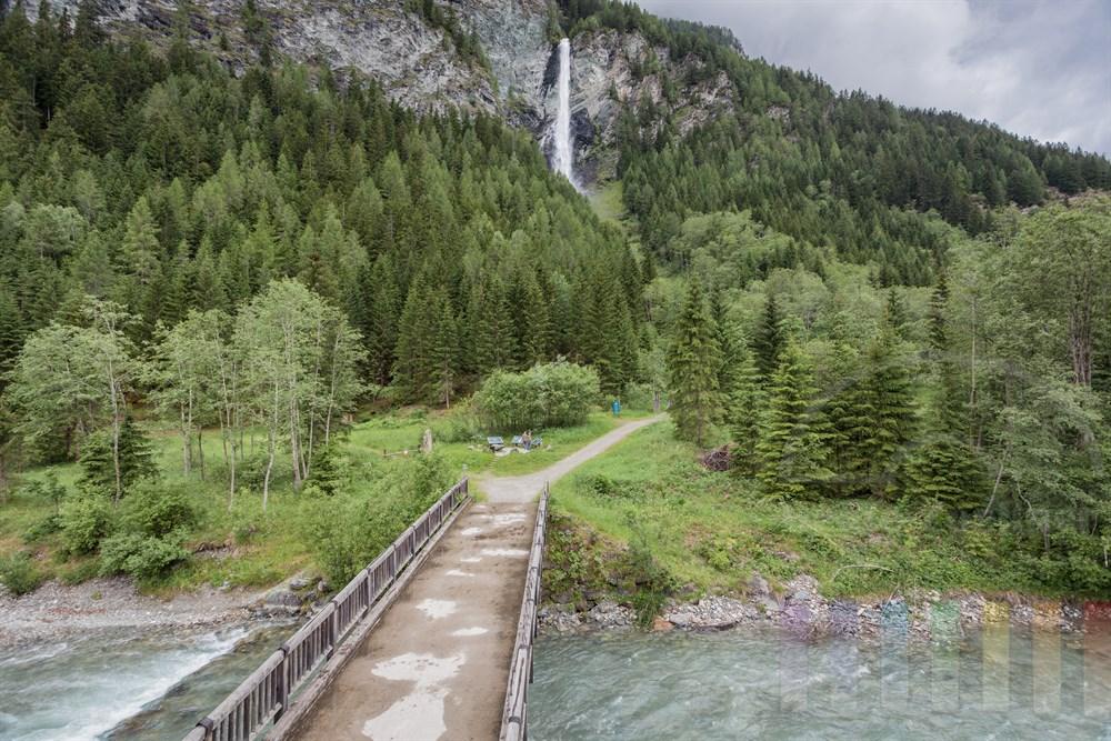 Brücke führt über den Fluss Möll zum Wasserfall Jungfernsprung - der Sage nach stürzte sich eine Jungfrau auf der Flucht vor dem Teufel die Felswand herab. Engel trugen sie zu Tal - die Jungfrau überlebte unverletzt. Der Wasserfall liegt in der Nähe von Heiligenblut am Fuße des Großglockner-Massivs