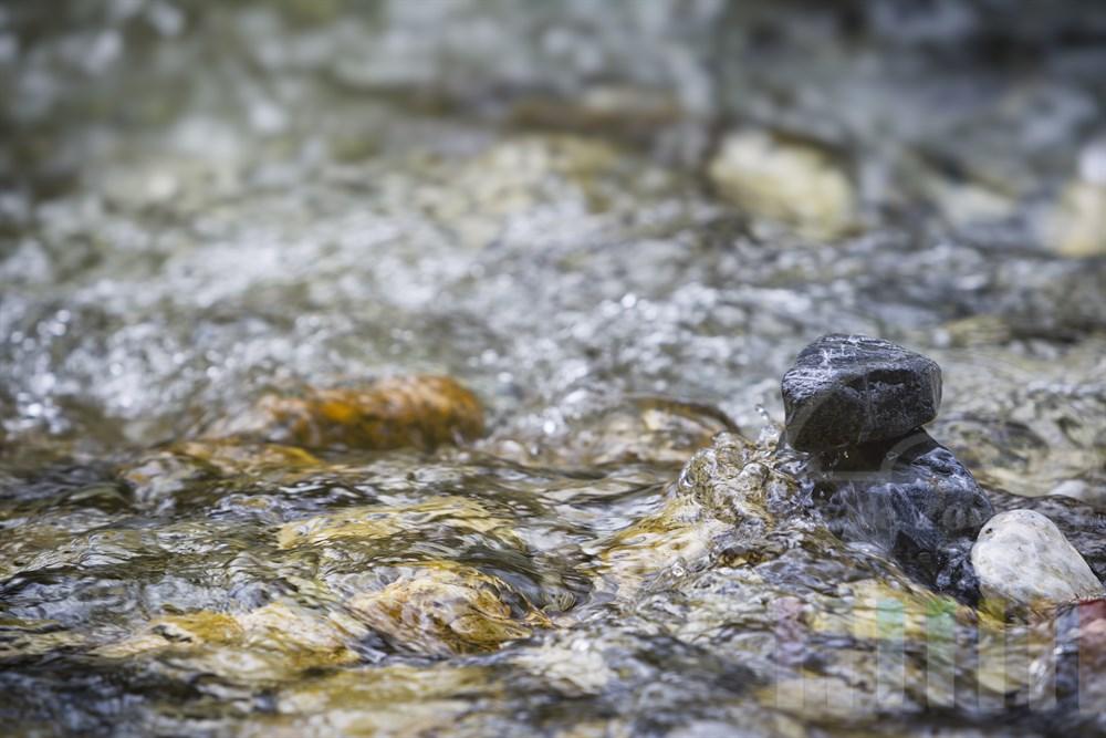 Kieselsteine bremsen das fliessende Wasser eines Gebirgsbaches (Kleinarler Ache)