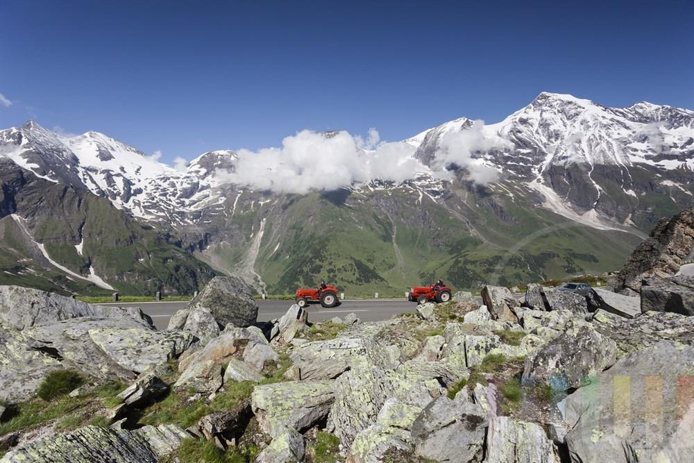 """Zwei historische rote Traktoren passieren die """"Hexenküche"""", ein Felssturzgebiet auf der Großglockner-Hochalpenstraße (Höhe ca. 2.400m) , sonnige Morgenstimmung"""