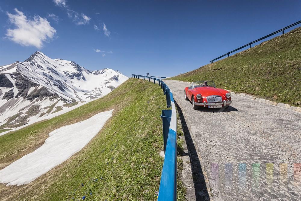 Knallrotes MG-Oldtimer-Cabrio fährt auf dem schmalen, historischen Teilstück der Großglockner-Hochalpenstraße talwärts. Es führt zum Bikers Point auf der Elweißspitze. Im Hintergrund schneebedeckte Berge, grüne Wiesen und blauer Himmel