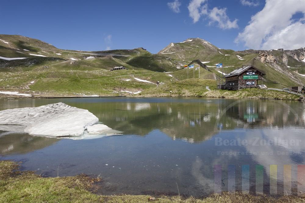 Bergsee Fuscher Lacke an der Großglockner-Hochalpenstraße. Im Hintergrund die Edelweiß-Spitze mit dem Bikers Point, sonniges Wetter. Ein großer Haufen Schnee liegt noch immer im Wasser des Sees.