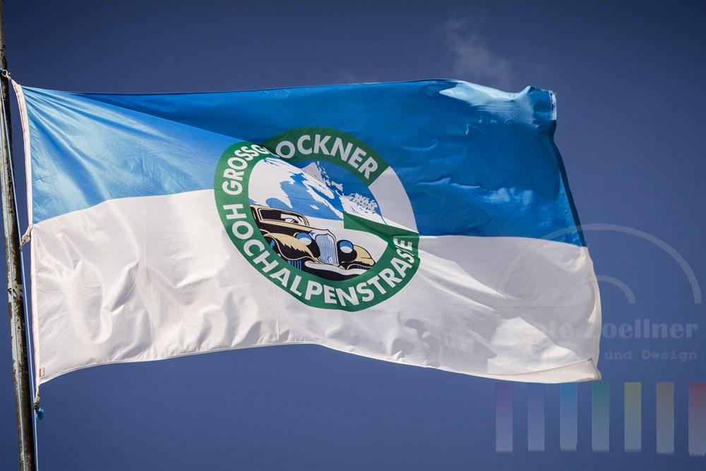 Im Wind flatternde Fahne mit dem Emblem der Großglockner Hochalpenstraße vor blauem Himmel im Sonnenschein