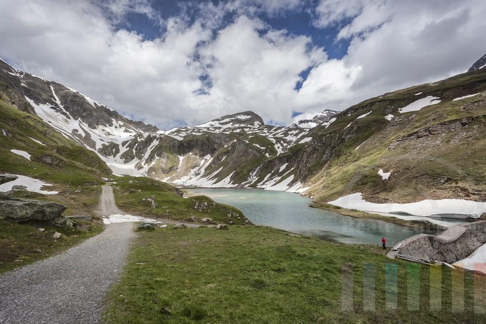 Blick über auf die Berggipfel und den kleinen Nassfeld-Stausee am Rand der Großglockner Hochalpenstraße, Ein Urlauber steht am Ufer und knipst ein Erinnerungsfoto
