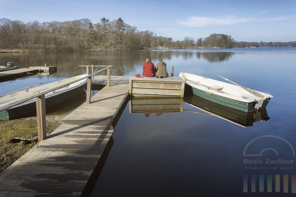 Paar sitzt auf einem Bootssteg am Lütjensee und genießt die ersten wärmenden Sonnenstrahlen des Frühlings. Mütze und Schal liegen hinter ihnen