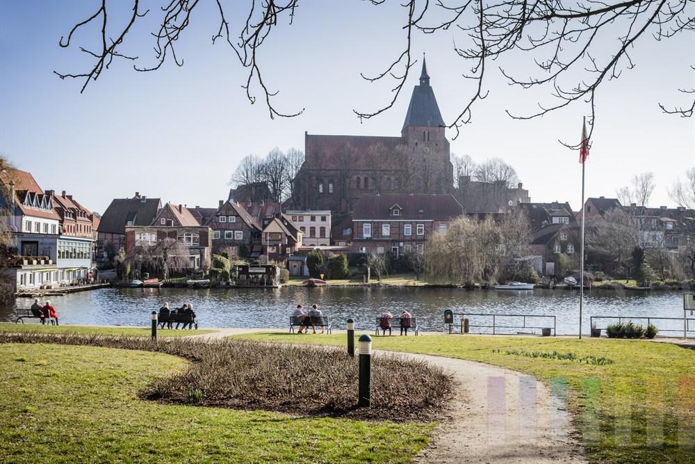 Blick über den Stadtsee auf die Altstadt von Mölln mit der St. Nicolai-Kirche. Menschen sitzen am Seeufer und genießen die Frühlingssonne
