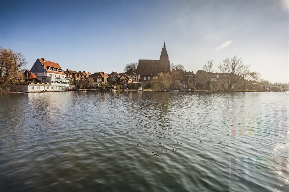 Blick über den Stadtsee auf die Altstadt von Mölln mit der St. Nicolai-Kirche, leichtes Gegenlicht