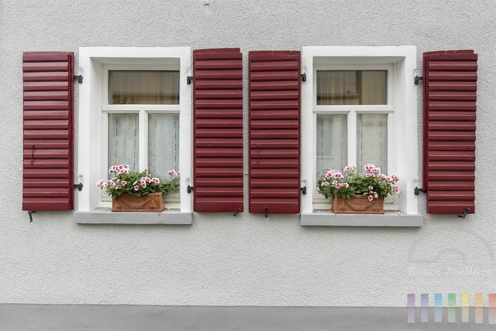 Zwei Fenster mit roten Fensterläden und Blumenkästen