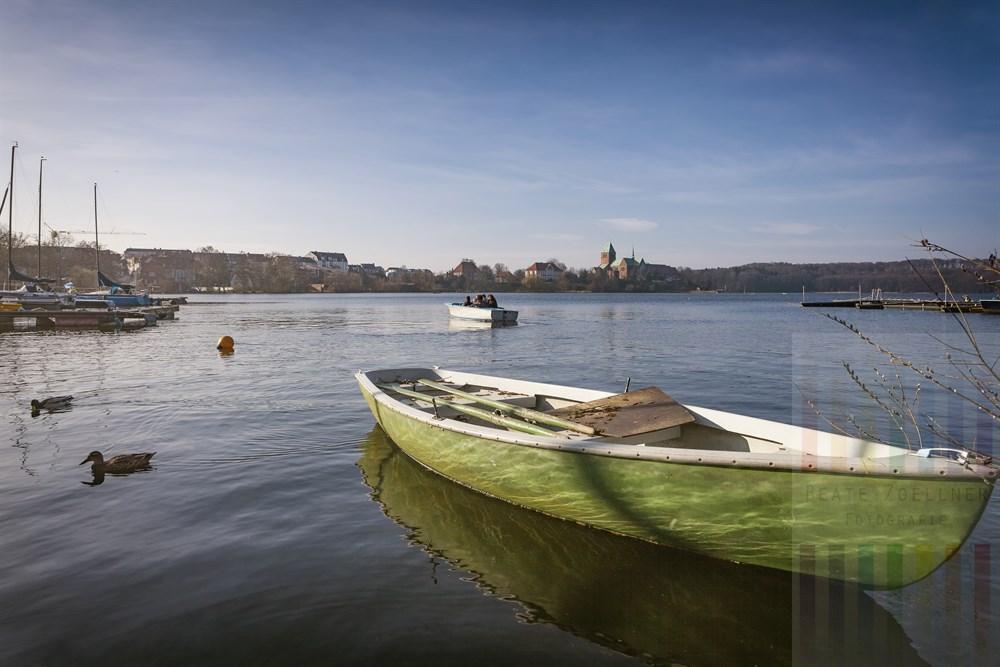 Grünes Ruderboot am Ufer des Ratzeburger See leuchtet im Licht der Frühlingsonne, im Hintegrund auf der Dominsel der Dom zu Ratzeburg