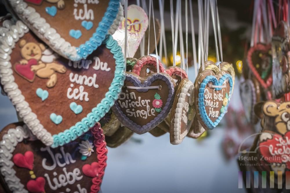 Lebkuchenherzen mit Liebessprüchen verpackt in Plastikfolie hängen an einem Stand auf dem Weihnachtsmarkt