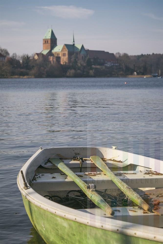 Blick über den Ratzeburger See auf den Dom, im Vordergrund liegt ein Ruderboot am Steg in der Frühlingssonne
