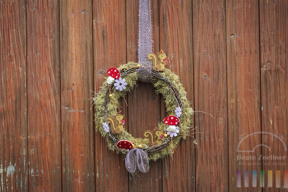 Herbstlich dekorierter Kranz an hölzerner Tür