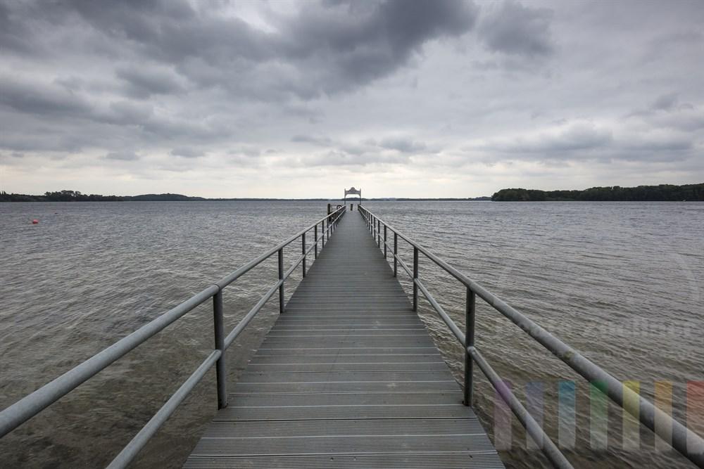 Schiffsanleger in Ascheberg am Großen Plöner See, dunkle Regenwolken am Himmel, Licht am Horizont