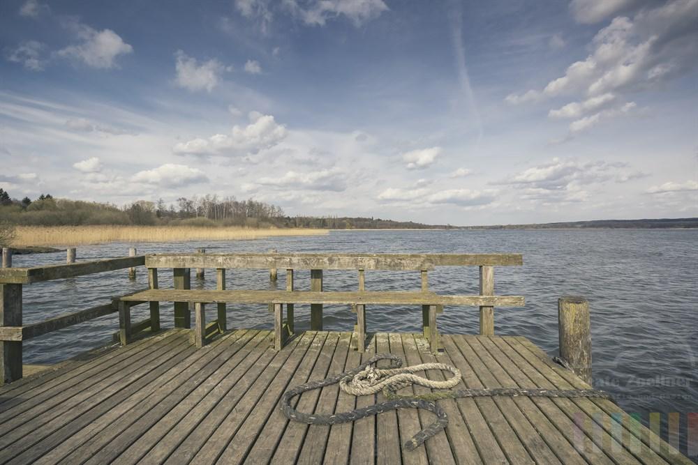 Schiffstaue liegen auf den Holzplanken eines Bootsanlegers am Ratzeburger See, frühlingshaft-sonnig