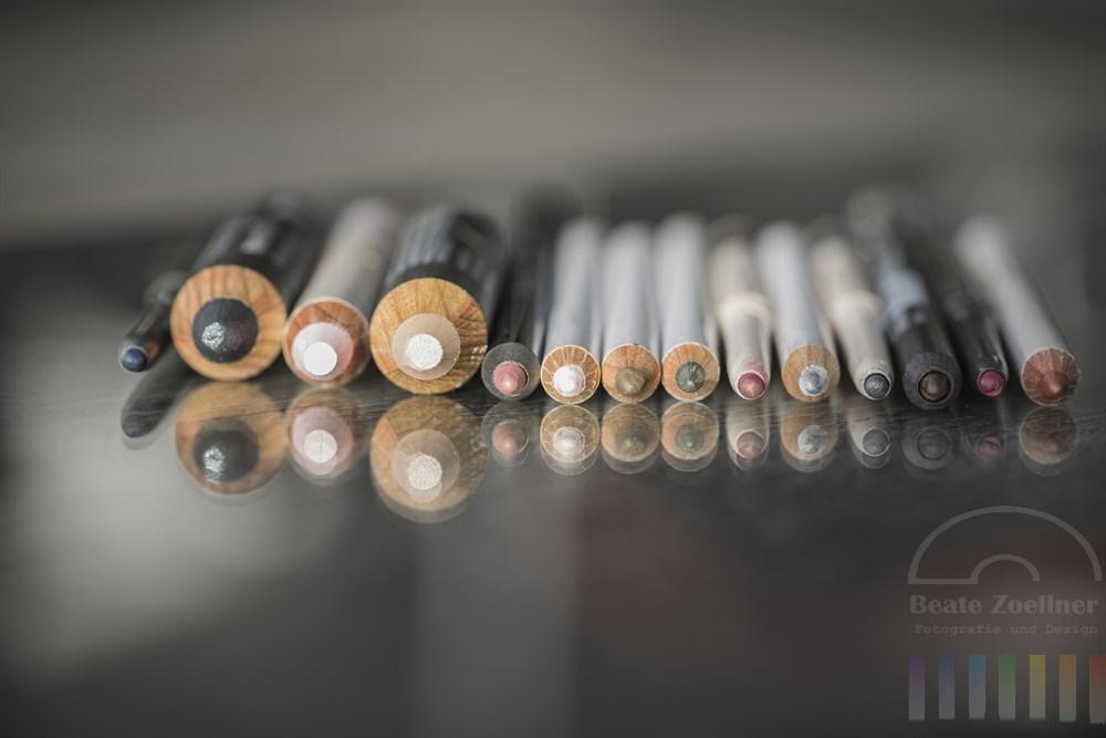 Auswahl von verschiedenen Schminkstiften auf Glasplatten, Frontalansicht, Makro